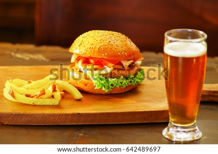 Delicious hamburger with beef, onion, tomato, lettuce and cheese with french fries and a glass of beer on wooden board