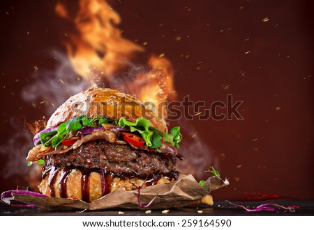 Delicious hamburger with fire flames on wooden background