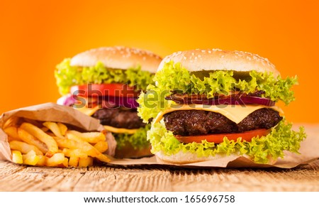Delicious hamburgers on wood - stock photo