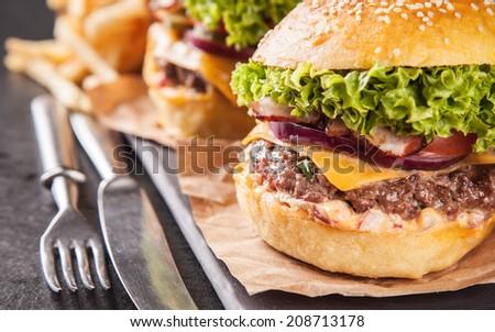 Delicious hamburgers served on black stone - stock photo
