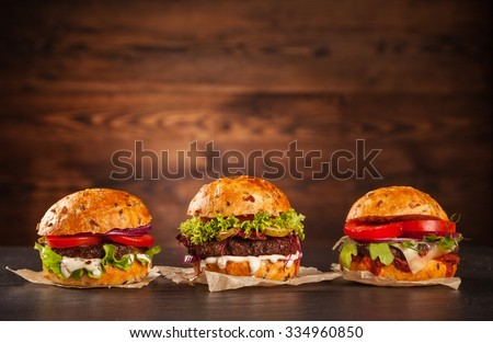 Delicious hamburgers served on wooden planks - stock photo
