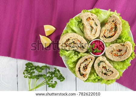 delicious healthy baked in oven minced white fish fillets roulade on fresh lettuce leaves with horseradish sauce in center on white plate, view from above