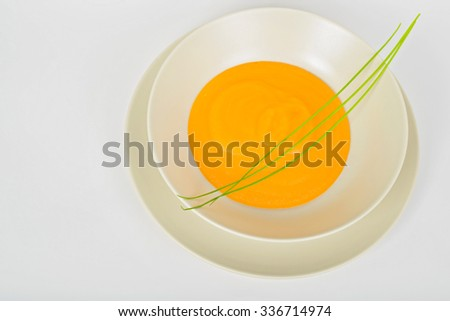 Delicious healthy pumpkin soup in a light dish. Top view. - stock photo