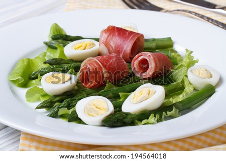 Delicious healthy salad with asparagus, eggs and ham on a white plate closeup. horizontal  - stock photo