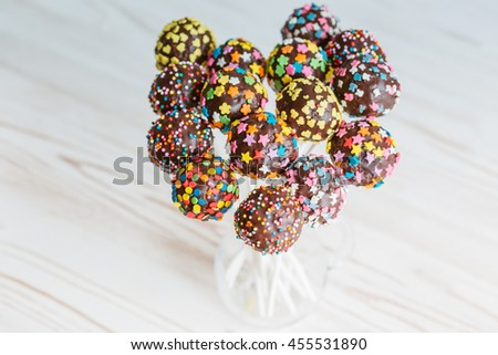 Delicious holiday colored cake pops in a glass - stock photo