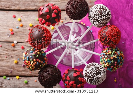 Delicious holiday colored cake pops in a glass closeup. horizontal top view
