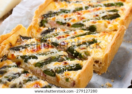 Delicious home made asparagus savory tart with pecorino and bacon on old wooden background.  Selective focus. - stock photo