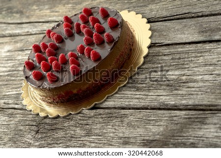 Delicious home made chocolate cake decorated with fresh raspberries on a golden plate placed on textured wooden desk with copy space ready for your text or message on the right side of the image. - stock photo
