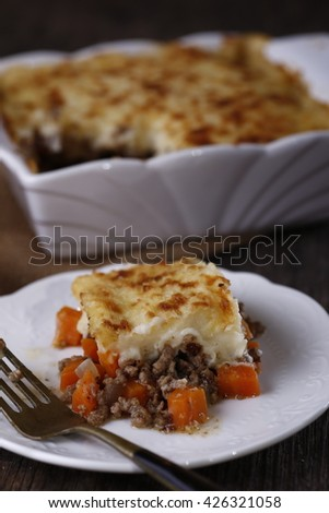 delicious home made shepherd pie in white porcelain against dark rustic wooden backdrop with burlap - stock photo