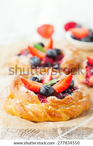 Delicious homemade buns with fresh berries on white wooden background, selective focus