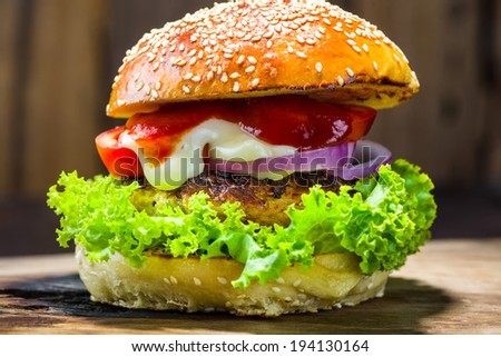 delicious homemade burger with vegetable on wood plate and wood as background - stock photo