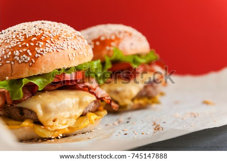 delicious homemade burgers with a juicy veal cutlet on a wooden table, against a red wall background