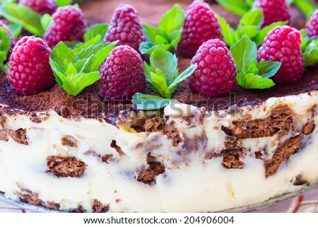 Delicious homemade cake garnished with raspberries and mint leaves - stock photo