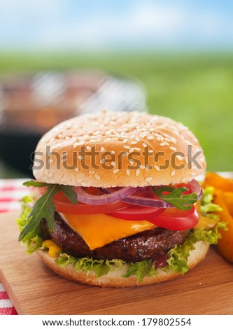 Delicious homemade cheeseburger on a summer picnic table outdoors with a succulent ground beef patty topped with melted cheese and garnished with fresh salad ingredients on a sesame bun - stock photo