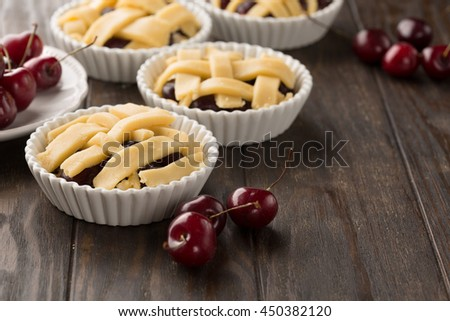 Delicious homemade cherry pies with fresh berries ready for baking, selective focus - stock photo