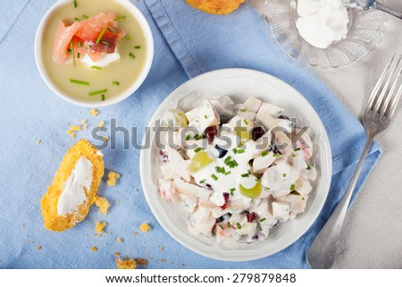 Delicious homemade chicken salad with yogurt, grapes, apples and cranberries on white plate with carrot buns on blue background, Selective focus.  Healthy eating. Top view.  - stock photo