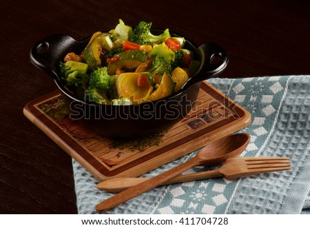 Delicious Homemade Colorful Vegetables Ragout with Zucchini, Carrots, Broccoli, Leek and Red Bell Pepper in Black Iron Stewpot with Wooden Spoon and Fork closeup on Blue Napkin - stock photo
