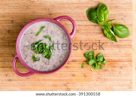 Delicious homemade cream of mushroom soup with minced fresh mushrooms garnished with chopped basil, overhead view in a ceramic bowl on a bamboo cutting board - stock photo