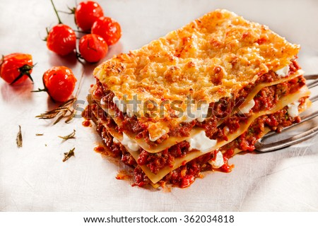 Delicious homemade Italian beef lasagne with roasted or oven-baked tomatoes on a serving spatula over a textured white background - stock photo