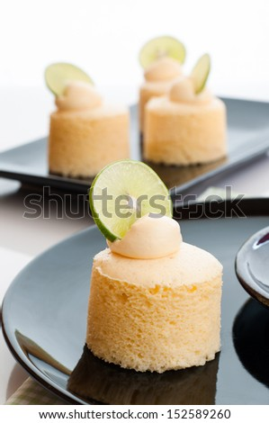 Delicious homemade japanese cheesecake garnished with butter cream and lime. - stock photo