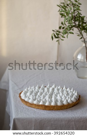 Delicious homemade lemon tart pie with green tea on rustic white table - stock photo