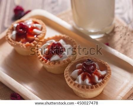 Delicious homemade mini cherry tarts and custard on wooden cutting board - stock photo
