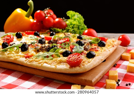 Delicious homemade pizza on table on black background