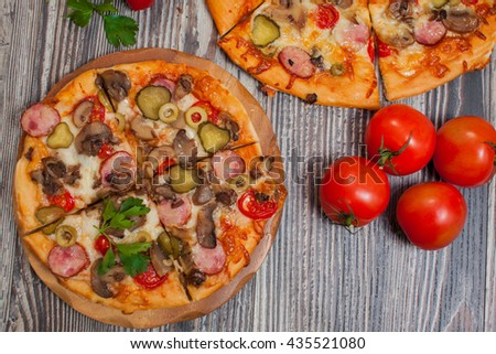 Delicious homemade pizza  with mushrooms and pepperoni , tomatoes and other ingredients on a wooden background . - stock photo