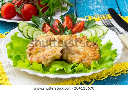 Delicious homemade pork cutlets with vegetables on a plate, napkin with yellow trim and cutlery on a blue wooden background. Selective focus - stock photo