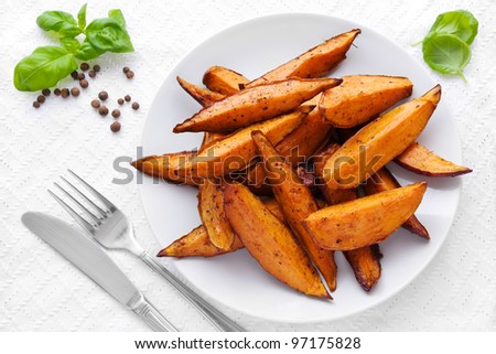 Delicious homemade sweet potato wedges on a plate - stock photo
