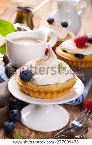 Delicious homemade tartlets served with lemon, lime curd cream, berries and meringue on old cutting board.  Selective focus. - stock photo