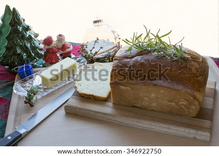 Delicious homemade white bread loaf on wood cutting board with butter and rosemary, Christmas set up on fabric table cloth for holiday dinner - stock photo