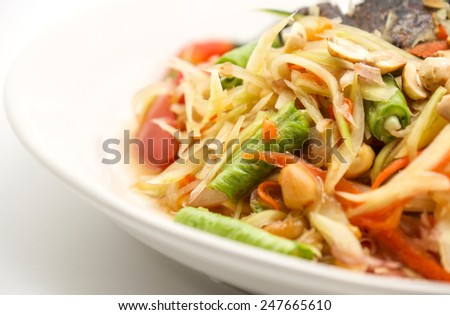 Delicious, hot and spicy green papaya salad for local Thai food background - stock photo