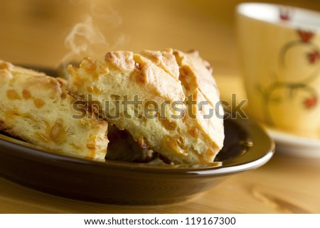 Delicious hot baked cheese biscuits on plate with cup of coffee. - stock photo