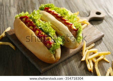 Delicious hot-dogs with French fries on wooden chopping board - stock photo