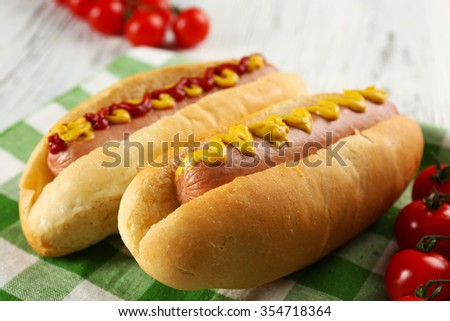 Delicious hot-dogs with tomatoes on green checkered cotton napkin, close up