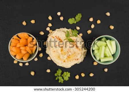 Delicious hummus background. Hummus, chickpeas, fresh carrot and cucumber vegetable on black background, top view. Traditional eastern cuisine. - stock photo