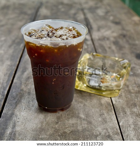 Delicious ice coffee americano  with cigarette on the old wooden table - stock photo