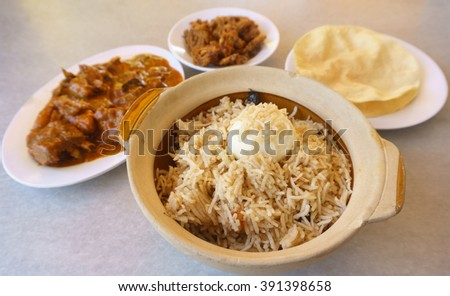 Delicious Indian biryani rice inside claypot on table setup.