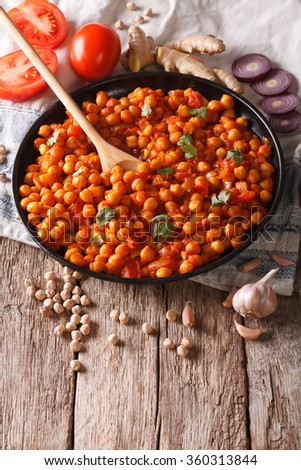 Delicious Indian cuisine: Chana masala with ingredients close-up on the table. vertical - stock photo