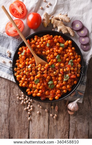 Delicious Indian cuisine: Chana masala with ingredients on the table. Vertical top view - stock photo
