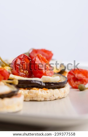 Delicious Italian appetizer of corn cracker topped with baked egg and juicy grilled aubergine and cherry tomatoes. - stock photo