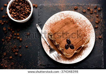 Delicious Italian dessert tiramisu with chocolate, cocoa and coffee beans on a black background. Top view with copy space - stock photo