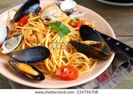 Delicious Italian pasta with squid and mussels in a plate, nutritious food - stock photo