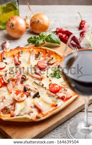 Delicious italian pizza served with red wine - stock photo