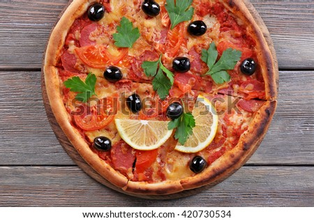 Delicious Italian pizza with black olives and slices of lemon on wooden table background