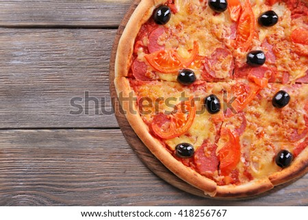 Delicious Italian pizza with black olives on wooden table background