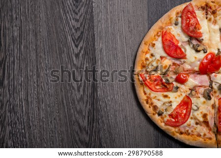 Delicious Italian pizza with ham and tomatoes on gray wooden table, top view  - stock photo