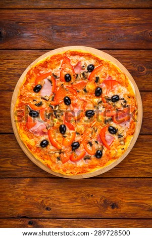 Delicious italian pizza with ham, peppers, mushrooms and black olives - thin pastry crust at wooden table background, above view