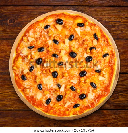 Delicious italian pizza with pineapple, chicken and black olives - thin pastry crust isolated at wooden background, above view - stock photo
